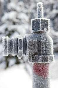 outdoor plumbing covered in frost winterizing sprinklers