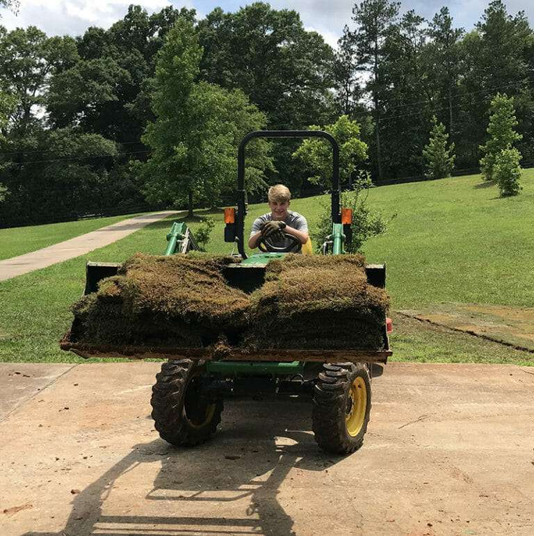 kid driving tractor front end loader full of sod
