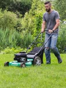 man pushing gas power lawn mower