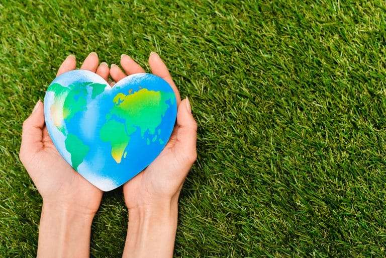 heart shaped globe in female hands on all natural grass