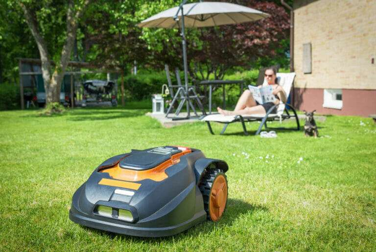 robotic lawn mower running while woman in background sits in chase lounge