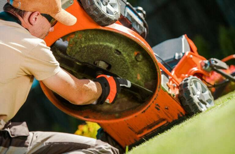 man checking lawn mower blade, fall lawn care