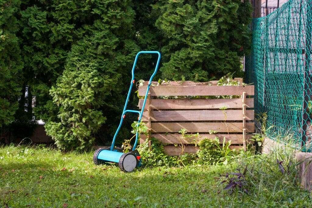 backyard with wood panel compost bin and hand run grass cutter