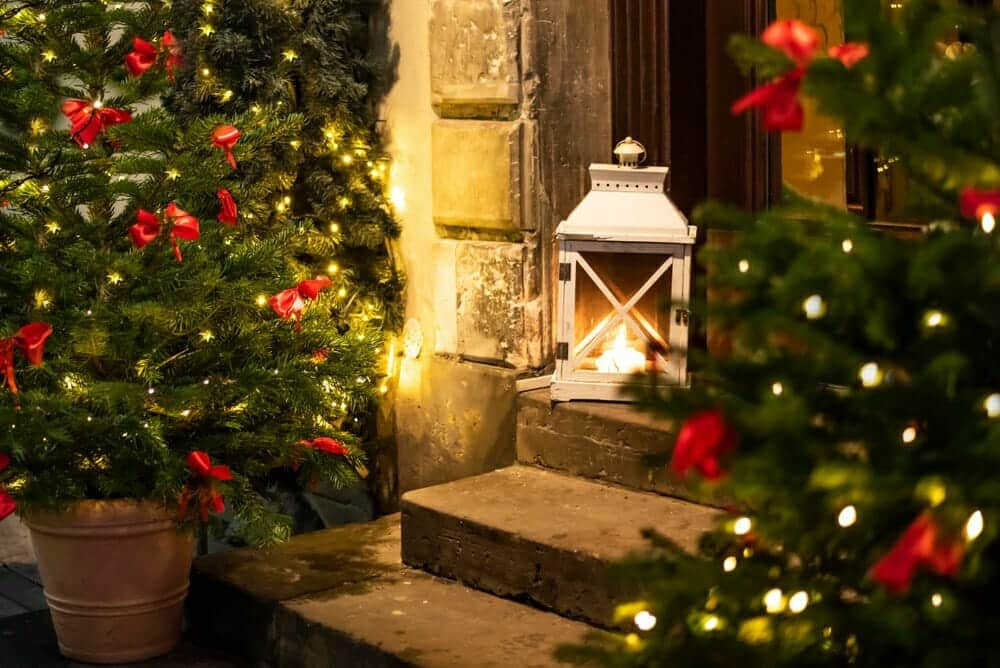 lantern and lighted tree on front porch, holiday yard decor inspiration
