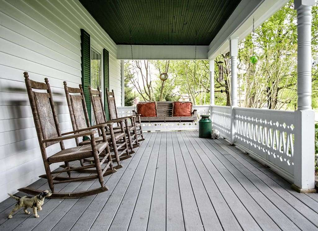 front porch with 4 rocking chairs and wooden swing