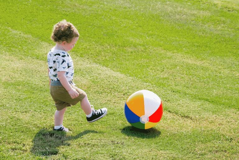 toddler playing with beach ball in backyard for fun