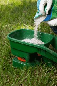 pouring fertilizer into dispenser on lawn