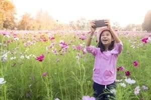 little girl taking photos on phone in field of flowers