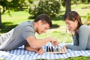 couple playing chess on picnic cloth in grass