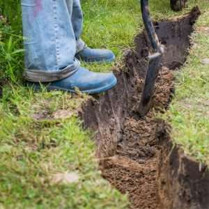 man with boots digging trench, Calhoun, GA sod for sale near me