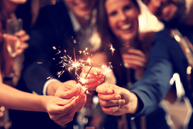 people with sparklers celebrating at holiday party