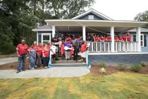 family and volunteers standing in front of new Atlanta Habitat for Humanity home with yard of newly installed sod donated by NG Turf