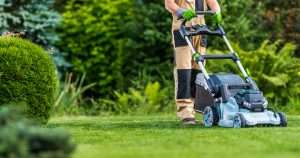 lawn care professional mowing lawn with push mower, healthy lawns