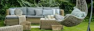 beautiful backyard with wicker garden furniture and fresh green grass