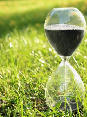 hourglass sitting in grass, how often to water lawn